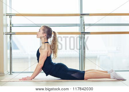 Photo of a beautiful female stretching on the floor sitting   mat.