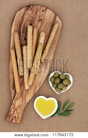 Appetiser snack with bread sticks on an olive wood board with green olives and oil in heart shaped bowls with leaf sprig.