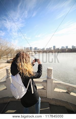 Woman traveler takes a photo of the landscape of the town near the lake in the park.
