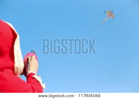 The girl in the red coat is holding on the rope of the flying snake, which soars in the sky.