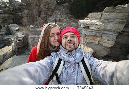 Beautiful couple making love selfie on a background of mountains in the park
