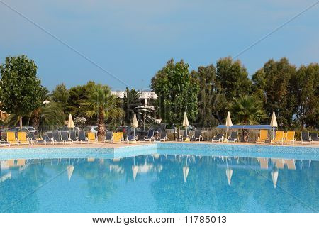 Big Blue Pool, Yellow Loungers And White Parasol Standing Near To The Pool, Many Palm Trees