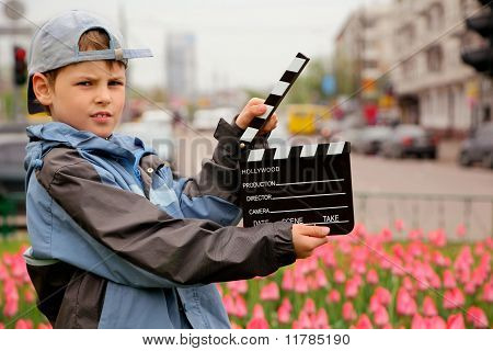 boy in jacket and cap with cinema clapper board in hands