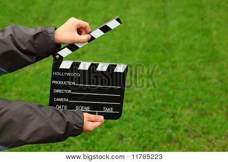 Cinema clapper board in hands of boy