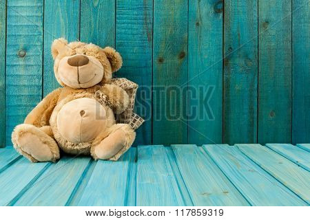 Teddy Bear On Turquoise Wooden Background. Baby Toys