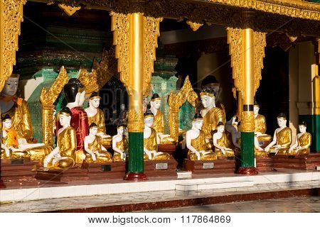 A Temple With Many Different Sized Buddhas At The Shwedagon Pagoda Glisten In The Early Morning Sun