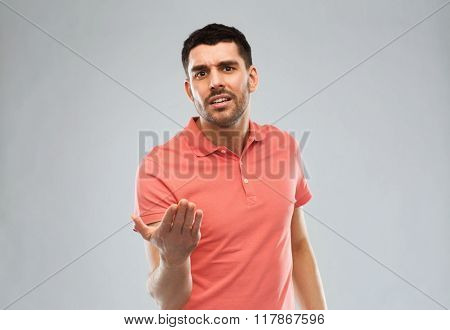 emotion, gesture, argue and people concept - arguing angry man proving something over gray