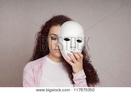 sad girl hiding face behind mask