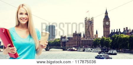 education, school, study abroad, drinks and people concept - smiling student girl with folders and cup of coffee over london city background