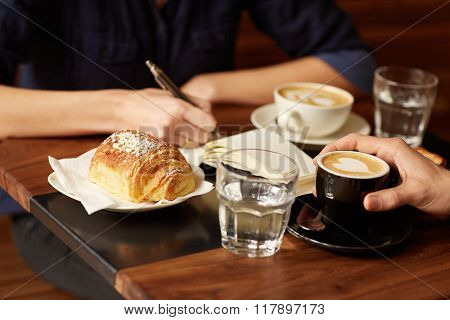 Two people at a coffee shop with one taking notes