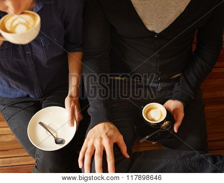 Hipster couple sitting next to each other with coffee