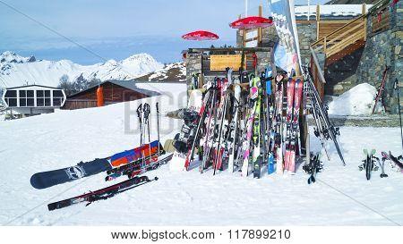 ski and snowboard by stone chalet on ski slopes