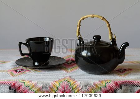 Cup With Saucer And Teapot Are On The Table.