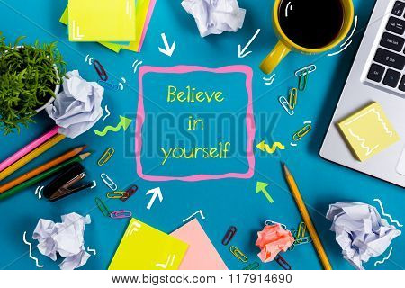Believe in yourself. Office table desk with supplies, white blank note pad, cup, pen, pc, crumpled p