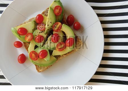 Avocado and rosa tomatoes on wholewheat toast with striped background