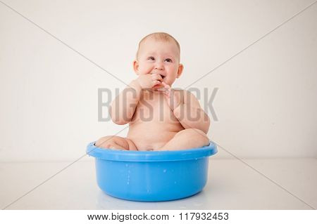 Happy one year old baby is bathed in a basin.
