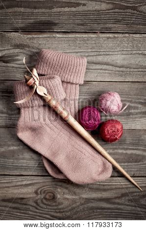 Retro Wooden Spindle And Purple Knitted Socks With  A Ball Of Yarn Shades Of Pink