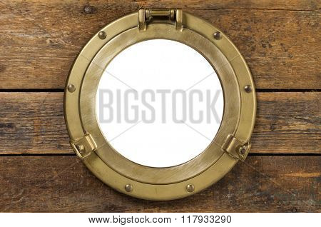 Vintage porthole with clipping path. old brass porthole in wooden wall, window isolated with clipping path