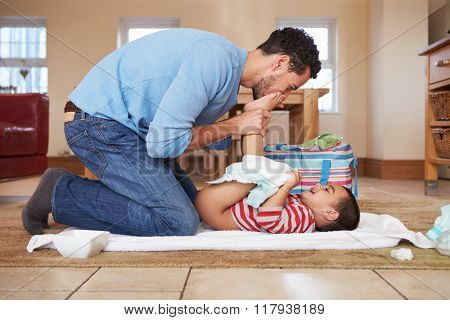 Father Changing Son's Diaper At Home