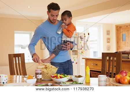 Father Carrying Son Whilst Making Salad In Kitchen