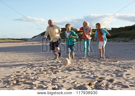 Grandparents Playing Soccer With Grandchildren On Beach