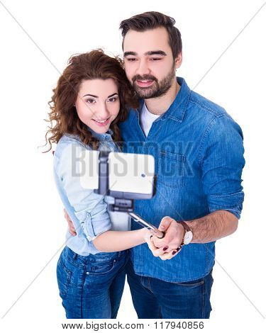 Young Happy Couple Taking Photo With Smart Phone On Selfie Stick Isolated On White