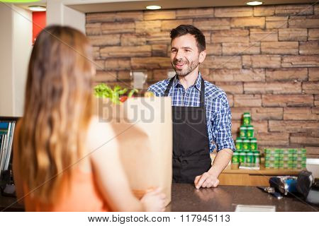 Male Cashier Being Friendly To A Customer