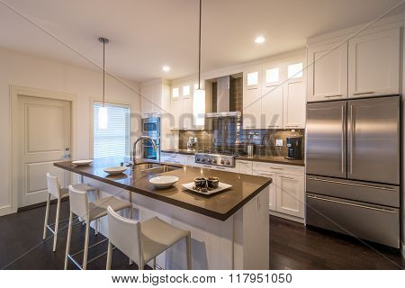Modern bright clean kitchen interior with stainless steel appliances in a luxury house. poster