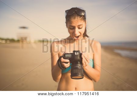 Surprised amazed woman photographer on vacation shooting.Photographer taking pictures with dslr camera on the beach.Professional travel photography.Memories on summer beach.Capturing moment of life