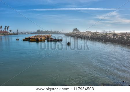 Dredge pipes floating in foggy marina.