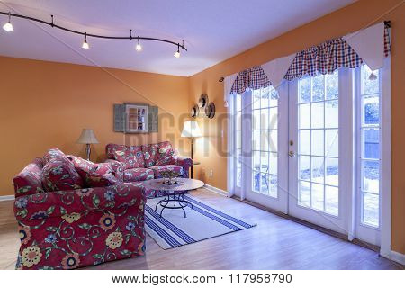 Colorful orange livingroom with french doors