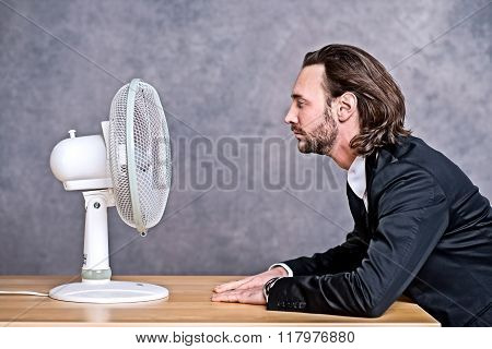 Business Man In Dark Suit Sitting In Front Of Ventilator