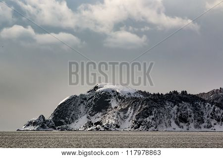 snowy stone promontory juts out in the sea