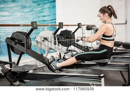 Fit brunette on drawing machine at the gym