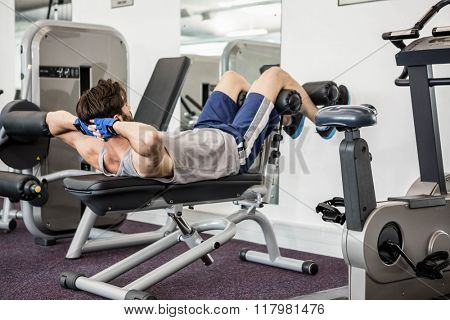 Man doing abdominal crunches on bench at the gym