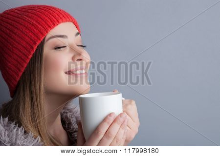 Attractive young woman is enjoying hot tea