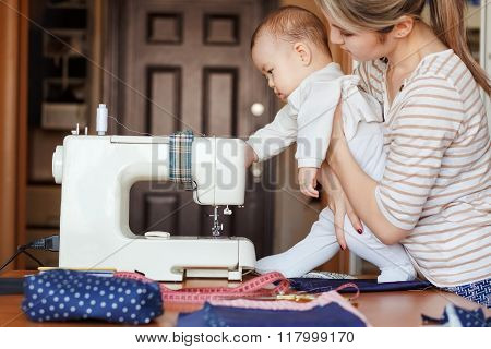 Small child learns new knowledge, along with his mother inspects sewing machine. Work at home, paren