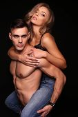 fashion studio photo of beautiful couple. gorgeous woman with long blond hair posing with handsome brunette man with sportive muscular torso poster