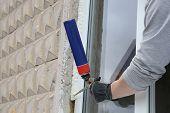 Worker's hand fix a window using polyurethane foam poster