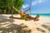 Happy and attractive woman with colorful sarongs and white wide-brimmed hat swinging on tropical white beach of Koh Rok Islands, Ko Lanta, Thailand paradise for snorkelers and divers. poster