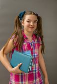 Portrait of cute schoolgirl smiling and holding book poster