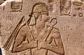 Ancient Egyptian hieroglyphic carving of a Pharaoh holding a flail, or fly whisk, and sceptre or crook.  Temple of Horus at Edfu, Egypt. poster