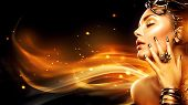 Burning woman head profile. Beauty Fashion model girl with Golden Makeup, accessories and nails on fire background. Gold earrings, rings, bracelets and manicure. Fashion art Hairstyle and make up poster