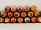 a frontal view of a set of colored pencils lying on a desk poster