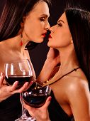 Lesbian women drinking red wine and kissing on nightclub. poster