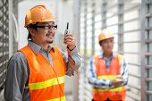 Asian foreman using walkie-talkie to communicate with coworkers poster