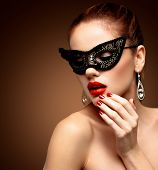 Beauty model woman wearing venetian masquerade carnival mask at party isolated on black background. Christmas and New Year celebration. Glamour lady with perfect make up poster