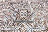 Close-up on a complex Roman tessera mosaic pavement center. Swastika Domus. Conimbriga in Portugal, is one of the best preserved Roman cities on the west of the empire. poster