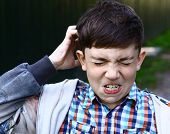 preteen handsome boy scratch his head itch because of lice invasion poster