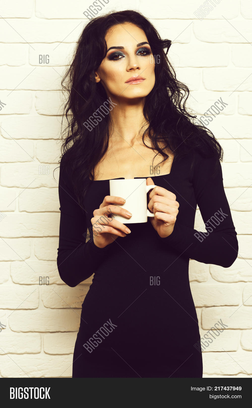 pretty cute sexy girl or beautiful young woman with fashion makeup on serious  face and curly long brunette hair in black dress with deep neckline on slim  ... 08b01dd16